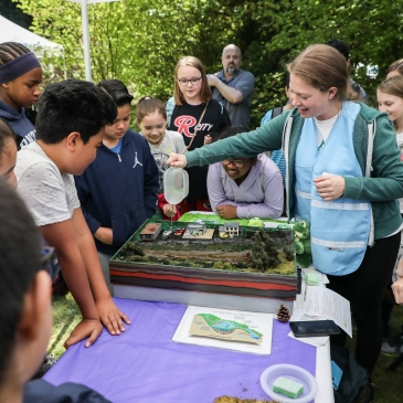 presenters demonstrate to a crowd of students around a table how water flows through a landscape using a watershed model