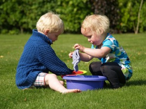 two children playing with a wash cloth and two buckets of water